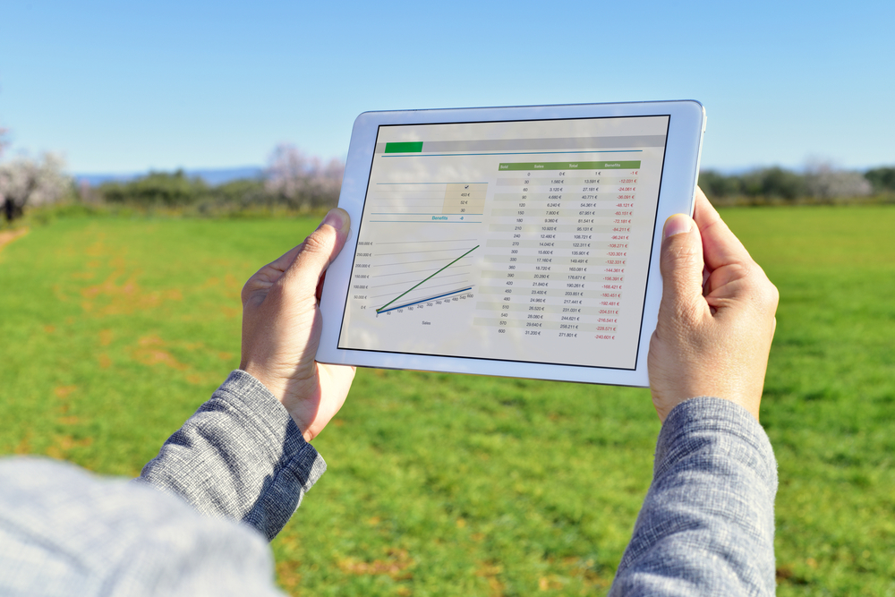 farmer observing charts on tablet computer